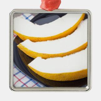 Nachtisch der süßen gelben Melonescheiben Quadratisches Silberfarbenes Ornament