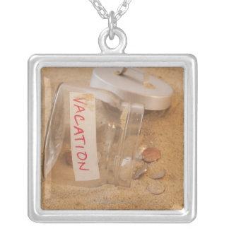 Nah oben vom Glas mit Münzen wurde auf Sand Versilberte Kette