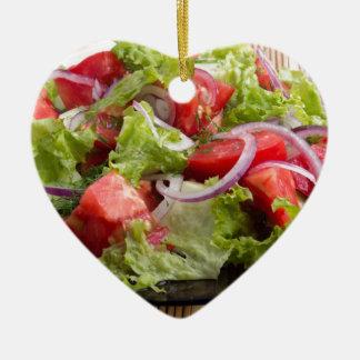 Nahaufnahmeplatte mit einem Salat der gehackten Keramik Herz-Ornament