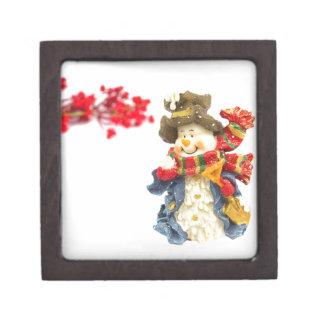 Niedliche Snowmanfigürchen mit roten Beeren auf Kiste