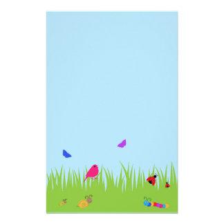 Niedliche Wanzen und Vogel im Gras mit blauem Briefpapier