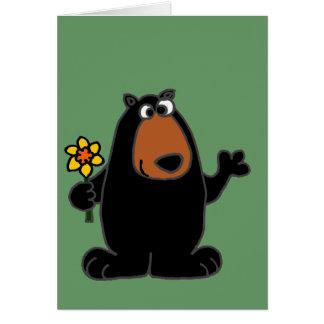 Niedlicher schwarzer Bär mit Narzissen-Cartoon Grußkarte