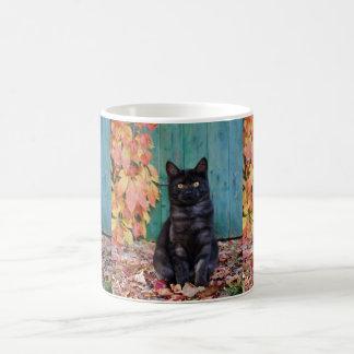 Niedliches schwarze Katzen-Kätzchen mit Rot Tasse