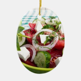Nützlicher vegetarischer Salat mit rohen Tomaten Ovales Keramik Ornament