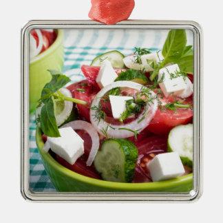 Nützlicher vegetarischer Salat mit rohen Tomaten Quadratisches Silberfarbenes Ornament