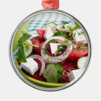 Nützlicher vegetarischer Salat mit rohen Tomaten Rundes Silberfarbenes Ornament