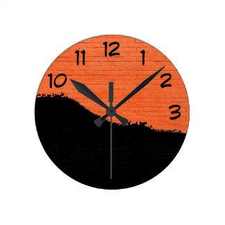 Orange Backsteinmauer mit schwarzer Schalen-Farbe Runde Wanduhr