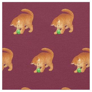 Orange Miezekatze-Katze, die mit Ball-Gewebe Stoff