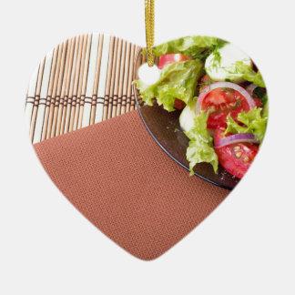 Platte mit frischem Salat der rohen Tomaten und Keramik Herz-Ornament