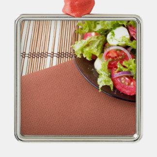 Platte mit frischem Salat der rohen Tomaten und Silbernes Ornament