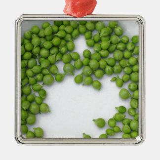 Reife grüne Erbsen auf einer Platte Silbernes Ornament