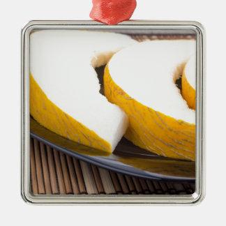 Saftige gelbe Melone auf hölzernem Hintergrund Quadratisches Silberfarbenes Ornament