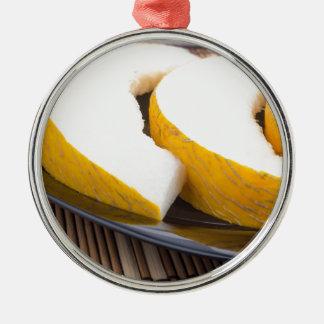 Saftige gelbe Melone auf hölzernem Hintergrund Rundes Silberfarbenes Ornament
