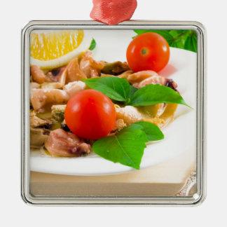 Salat der geblichenen Stücke Meeresfrüchte auf Quadratisches Silberfarbenes Ornament