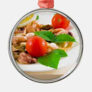 Salat der geblichenen Stücke Meeresfrüchte auf Rundes Silberfarbenes Ornament