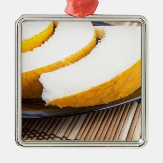 Scheiben der saftigen gelben Melone auf einer Quadratisches Silberfarbenes Ornament