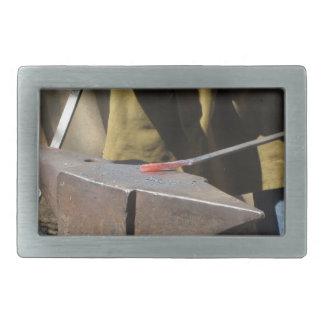 Schmied, der manuell das flüssige Metall schmiedet Rechteckige Gürtelschnallen