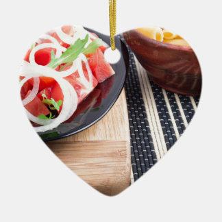 Schwarze Platte mit frischem Salat der Tomaten, Keramik Herz-Ornament