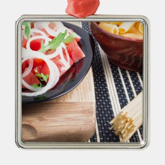Schwarze Platte mit frischem Salat der Tomaten, Quadratisches Silberfarbenes Ornament