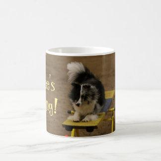 Sheltie, das an einer Agility-Schaukel hängt Tasse