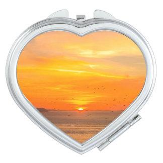 Sonnenuntergang-Küste mit orange Sun und Vögeln Schminkspiegel