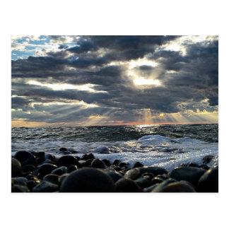 Sunbeams auf einem felsigen Ufer Postkarte