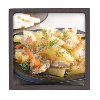 Teller der gedämpften Kartoffeln mit Fleisch und Schmuckkiste