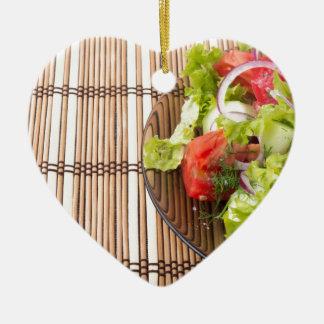 Vegetarischer Salat vom Frischgemüse auf einem Keramik Herz-Ornament