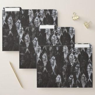 Versteinerte weiße Fische auf schwarzem Papiermappe