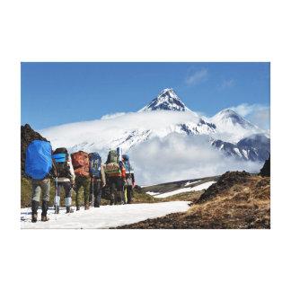 Wanderer, die auf Berg auf Hintergrundvulkanen Leinwanddruck