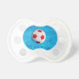 Wasserball, der in blauen Swimmingpool schwimmt Schnuller