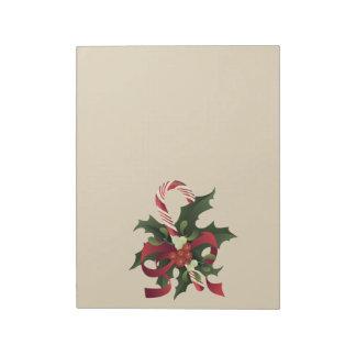 Weihnachtszuckerstange in einem Mistelzweig und Notizblock