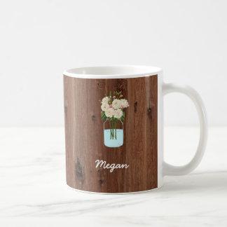 Weißes Blumen-Maurer-Glas auf rotem Holz Tasse