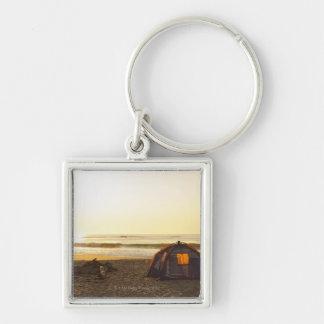Zelt und brennen Lagerfeuer auf dem Strand aus Silberfarbener Quadratischer Schlüsselanhänger