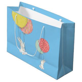 Zwei kleine Häschen, die mit Ballonen schwimmen Große Geschenktüte